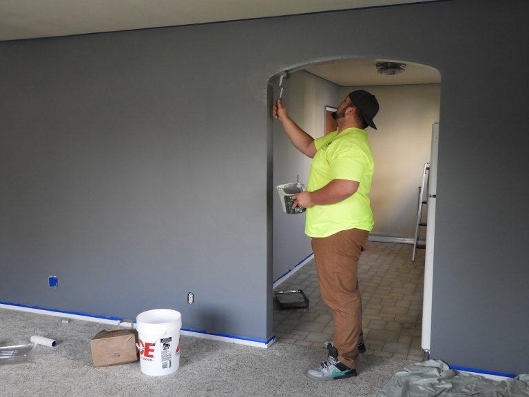 איש עם חולצה צהובה, צובע את הבית